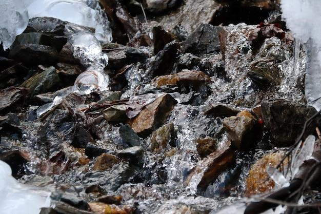 O córrego da montanha flui através de pedras, neve e pingentes de gelo