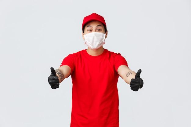 O correio asiático de sorriso alegre no tampão e no t-shirt vermelhos esticam as mãos para a frente para tomar o pacote do cliente na empresa de entrega. entregue o cara de uniforme, máscara e luvas médicas e receba mercadorias