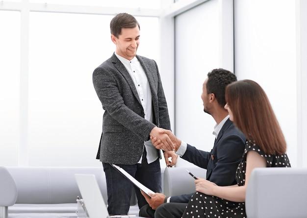 O corretor de imóveis e o jovem casal apertando as mãos um do outro