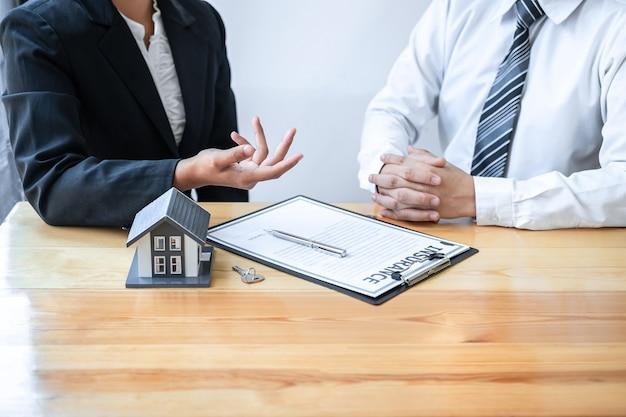 O corretor de imóveis está apresentando empréstimo e doação de casa ao cliente após discutir e assinar o contrato de acordo com o formulário de inscrição aprovado, seguro residencial e conceito de investimento imobiliário.