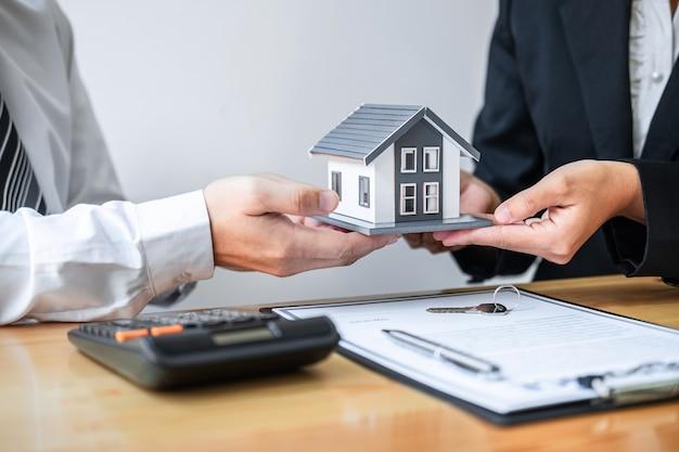 O corretor de imóveis está apresentando empréstimo para casa e dando casa ao cliente após a assinatura do contrato