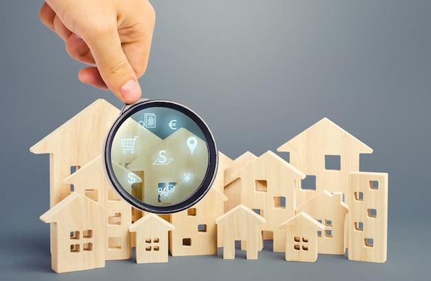 O corretor de imóveis examina casas com uma lupa
