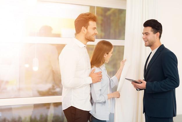 O corretor de imóveis mostra a propriedade para um jovem casal
