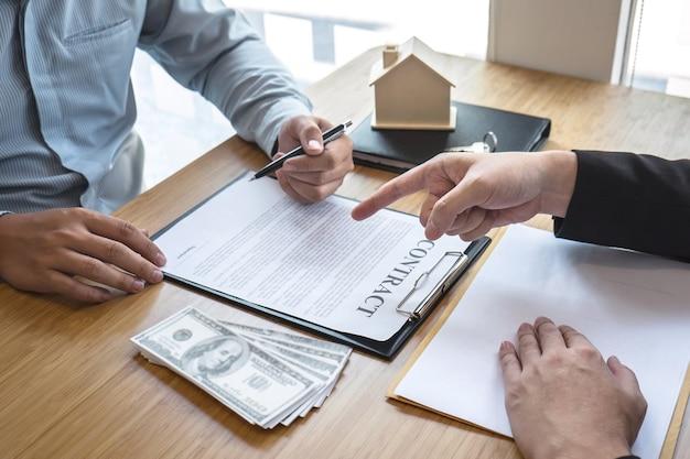 O corretor imobiliário está apresentando o empréstimo e a entrega das chaves da casa ao cliente após a assinatura do contrato de compra da casa com o formulário de pedido de propriedade aprovado.