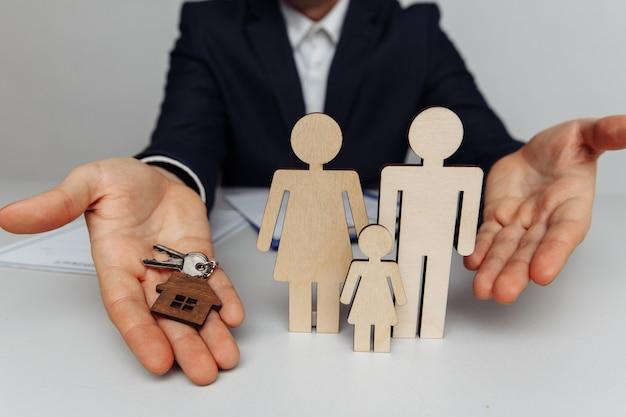 O corretor tem as chaves de uma casa. figuras de madeira de uma família à frente.