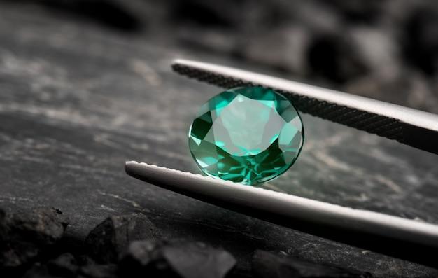 O corte de jóias de pedras preciosas esmeralda.