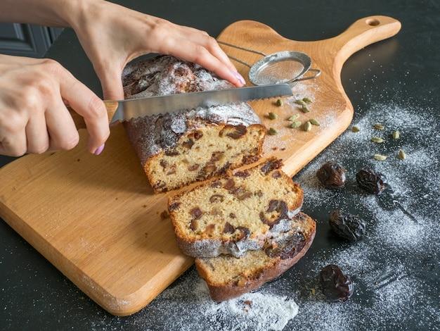 O corte dos pedaços de bolo de data. pão caseiro de datas com nozes em uma mesa preta