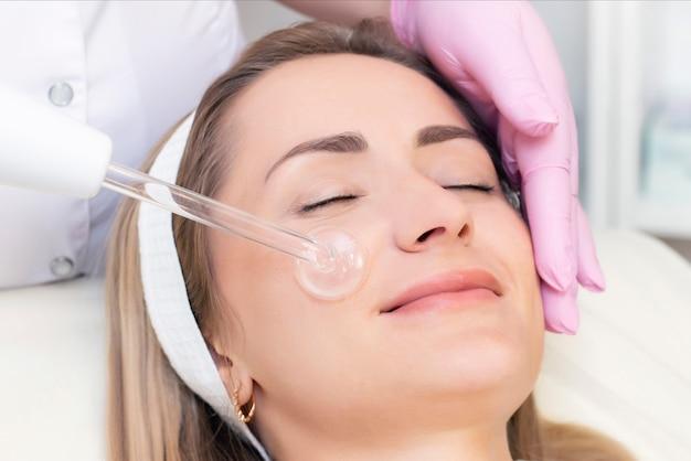 O cosmetologista realiza um procedimento de corrente de pulso no rosto de uma mulher jovem.