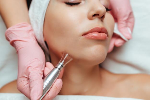 O cosmetologista realiza uma aspiração de rosto