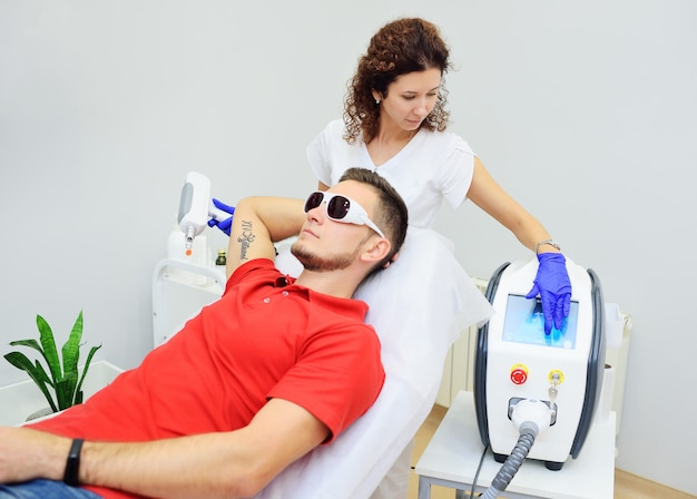 O cosmetologista remove a tatuagem do paciente com um laser de neodímio.