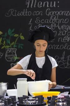 O cozinheiro chefe bonito da menina em um avental preto e o chapéu de um cozinheiro agita com colher em uma bacia branca