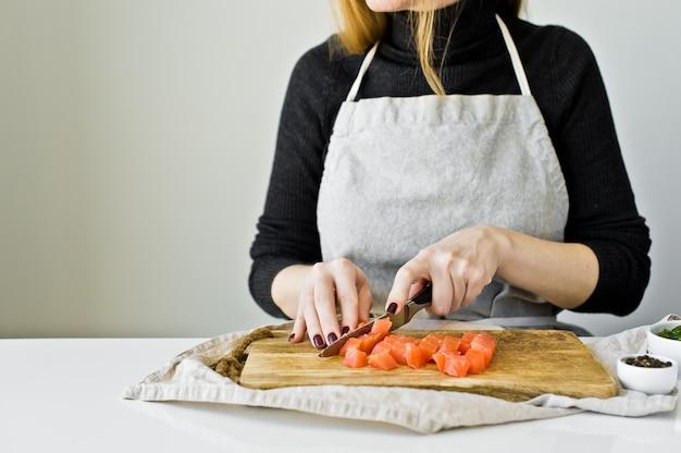 O cozinheiro chefe corta a faixa salmon em uma placa de desbastamento de madeira.