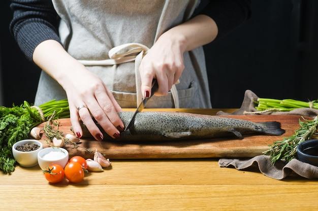 O cozinheiro chefe corta a truta crua em uma placa de desbastamento de madeira.