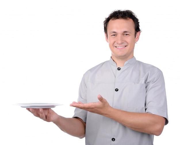 O cozinheiro chefe cozinha no uniforme que entrega uma placa branca.