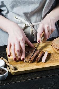 O cozinheiro chefe das mãos cortou o bife em uma placa de desbastamento de madeira.