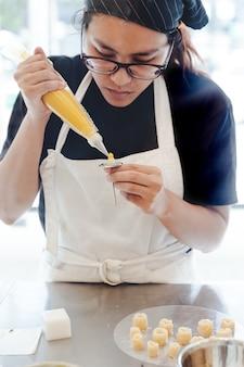 O cozinheiro chefe de pastelaria da mulher pretende em fazer uma flor amarela da manteiga para a decoração do bolo.
