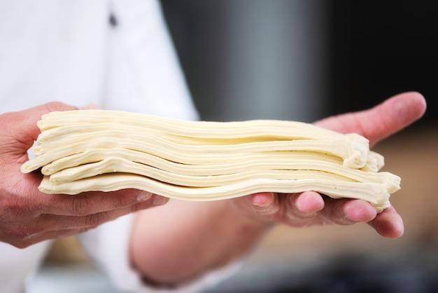 O cozinheiro chefe de pastelaria que mostra a massa de folha cobre pronto para ser rolado para produzir o croissant.