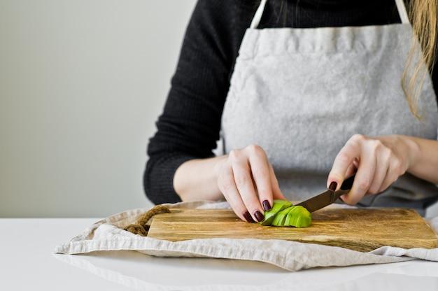 O cozinheiro chefe descasca o abacate em uma placa de desbastamento de madeira.