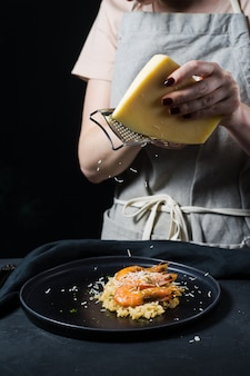 O cozinheiro chefe fricciona o parmesão no risoto italiano com camarão em uma placa preta.