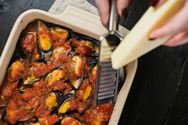O cozinheiro chefe fricciona o queijo nos mexilhões no molho de tomate.