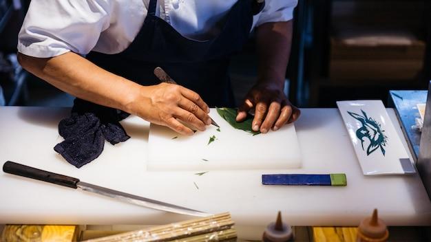 O cozinheiro chefe japonês criou a arte da folha pela faca. cortar uma folha para decorar uma refeição na placa de desbastamento branca.