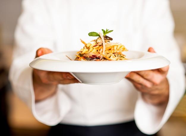 O cozinheiro chefe que guardara a salada de massa molhando molhando, apronta-se para servir.