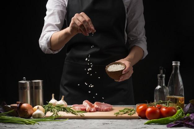 O cozinheiro chefe salga a bandeja da grade do bife. preparar a carne fresca ou carne de porco.
