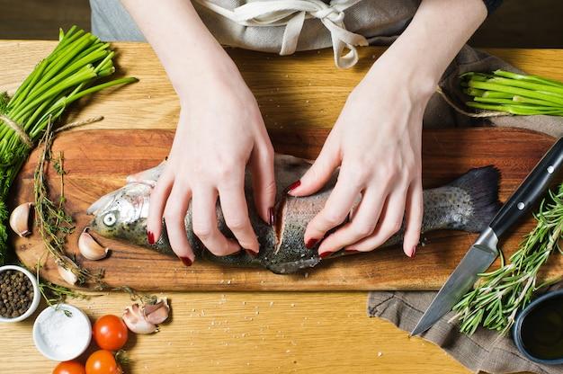 O cozinheiro chefe salga truta crua em uma placa de desbastamento de madeira. ingredientes alecrim, limão, tomate, alho, sal, pimenta.