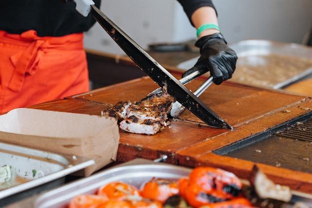 O cozinheiro corta a carne no mercado de rua