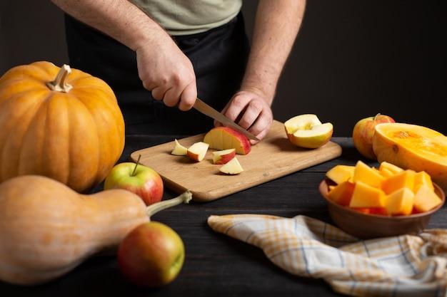 O cozinheiro corta a maçã em pedaços para assar.