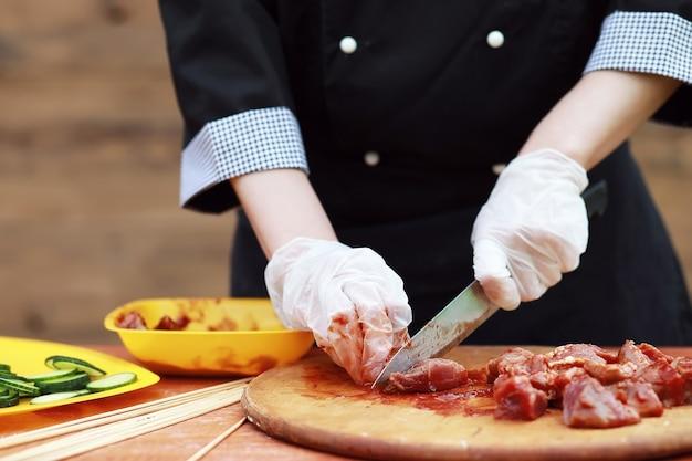 O cozinheiro corta carne para assar churrasco na mesa