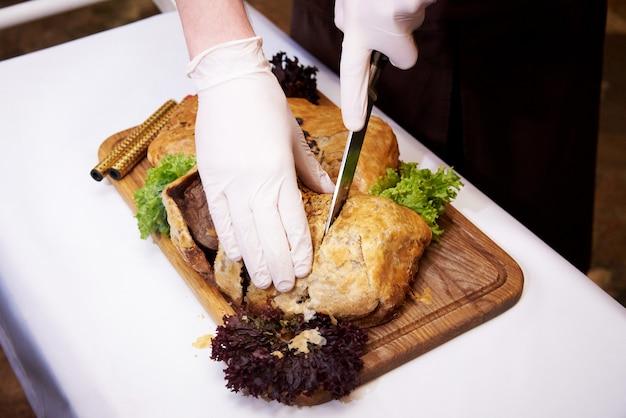 O cozinheiro corta o prato quente cozinhado em uma bandeja em um restaurante.