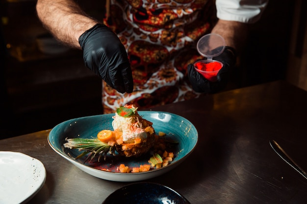 O cozinheiro, cujas mãos estão vestidas com luvas pretas, polvilha a salada cozida, que fica na metade do abacaxi com tempero vermelho.
