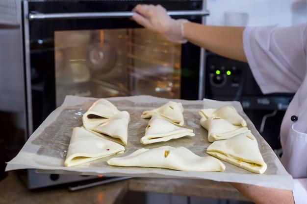 O cozinheiro da mulher coloca o queijo sopra na folha de cozimento no forno. pastelaria fresca no café