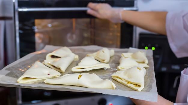 O cozinheiro da mulher coloca o queijo sopra na folha de cozimento no forno.