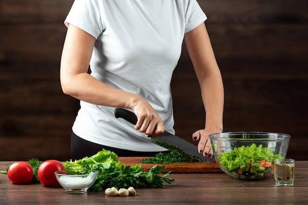 O cozinheiro da mulher corta vegetais para a preparação da salada na madeira.