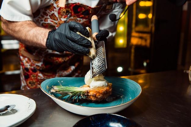 O cozinheiro esfrega o queijo em um ralador sobre a salada cozida.