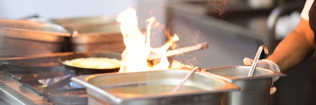 O cozinheiro está cozinhando no fogão com fogo aberto