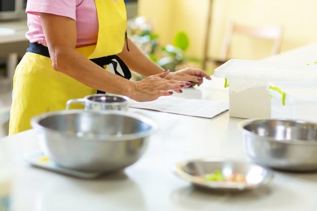 O cozinheiro está estudando a receita antes de cozinhar