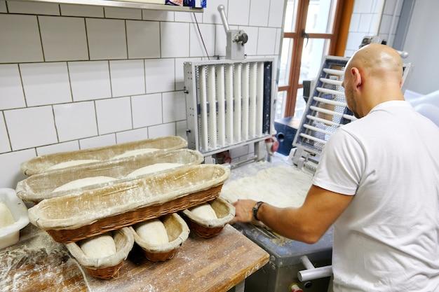 O cozinheiro faz fatias de massa e coloca em fila na tigela, bolos, produtos de farinha