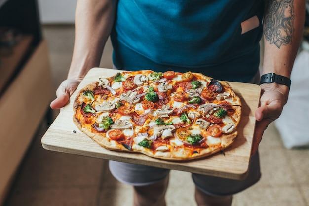 O cozinheiro segura uma bandeja de madeira ou uma tábua com pizza caseira orgânica crocante, coberta com vegetais, vegetais e queijo