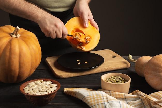 O cozinheiro separa o grão da abóbora cortada ao meio. sobre uma mesa de madeira preta estão abóboras inteiras de diferentes tamanhos. sementes em duas tigelas.