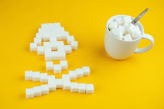 O crânio de ossos feito de cubos de açúcar e uma xícara branca cheia de açúcar com uma colher em um fundo amarelo. o açúcar mata e o conceito de diabetes.