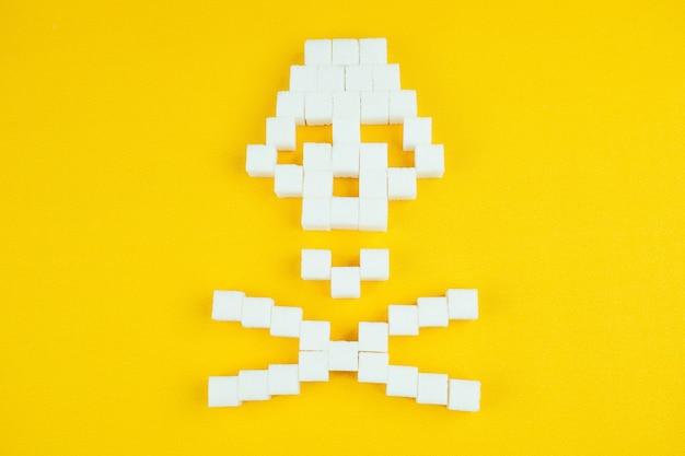 O crânio de ossos feito de cubos de açúcar em um fundo amarelo. açúcar mata e conceito de diabetes