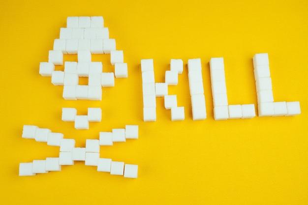 O crânio de ossos feito de cubos de açúcar em um fundo amarelo. o açúcar mata e o conceito de diabetes. a palavra matar vem do açúcar
