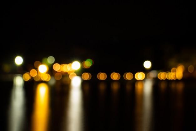 O crepúsculo da noite borrou o bokeh claro do ouro que reflete no fundo do sumário da água de superfície do mar.