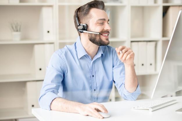 O criador alegre da linha direta com fone de ouvido se comunica com clientes por meio de bate-papo online na frente da tela do computador