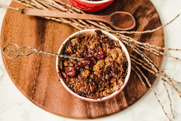 O crumble da cereja com o granola do chocolate servido serviu em placas vermelhas repartidas em partes. vista superior. fechar-se.
