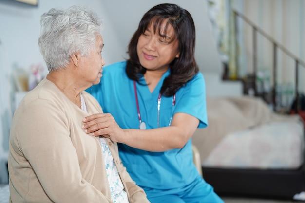 O cuidado asiático da enfermeira, ajuda e apoia o paciente sênior da mulher no hospital.
