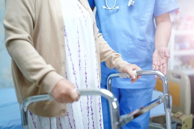 O cuidado asiático do doutor do fisioterapeuta da enfermeira, ajuda e apoia o paciente idoso da mulher adulta.